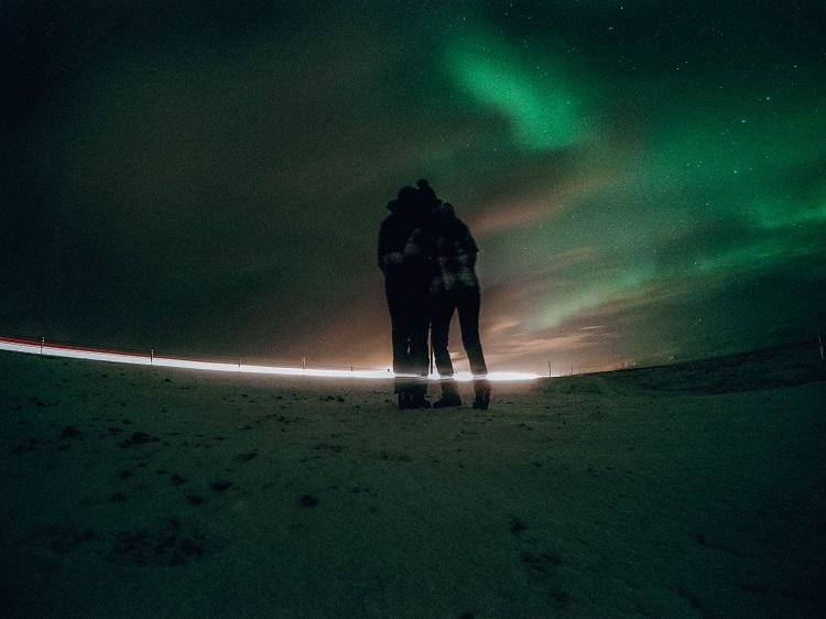 Couple watching the Northern Lights in Iceland during winter