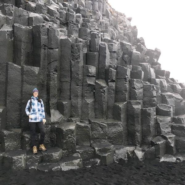Girl standing on basalt columns at Vik Beach in Iceland