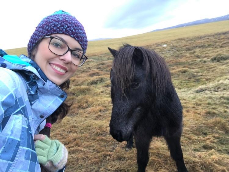 Girl posing with an Icelandic horse