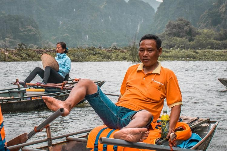 Tam Coc, Ninh Binh boat tour. Vietnamese man rowing the boat with his feet