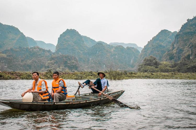 Vietnamese man rowing the boat with his feet in Ninh Binh, Vietnam