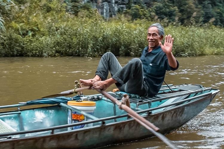 Vietnamese man waving his hand while rowing the boat with his feet in Tam Coc, Ninh Binh