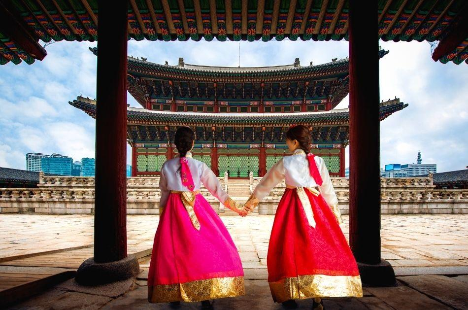 two korean girls dressed in hanbok holding hands in front of a palace in Seoul