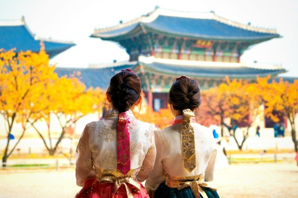 two korean girls dressed in hanbok in front of a palace in Seoul