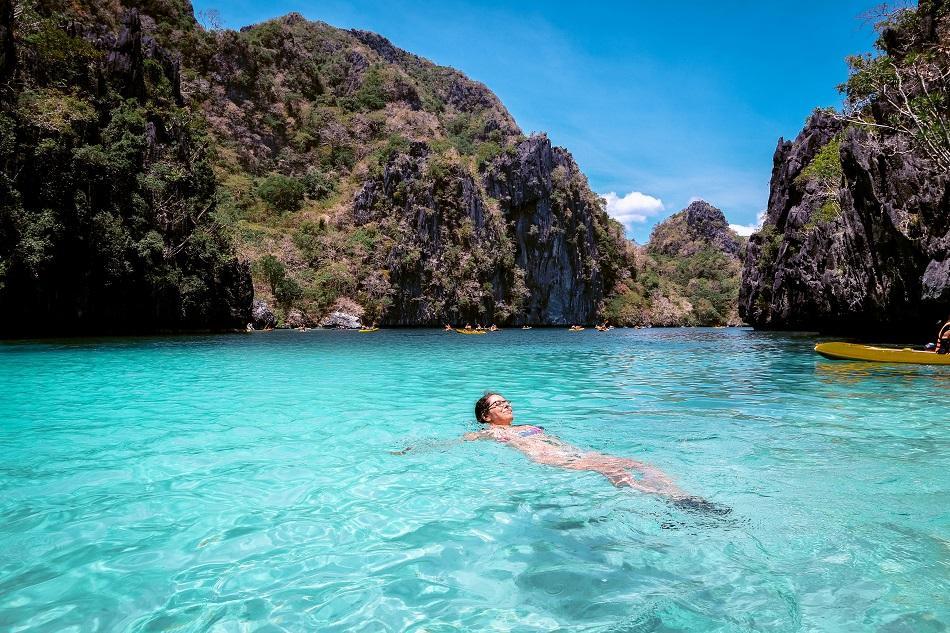 Girl swimming at Big Lagoon El Nido