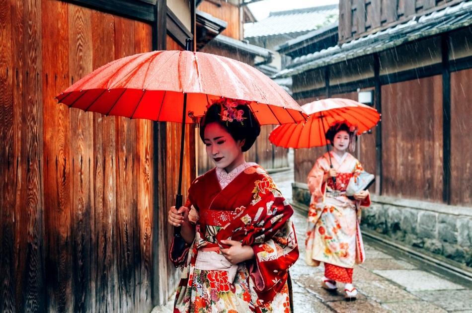 2 geishas with red umbrellas in Kyoto
