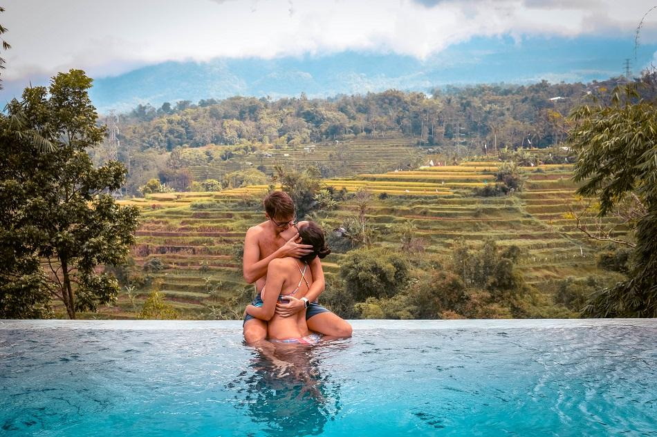 Couple on the edge of an infinity pool overlooking the rice fields in Bali