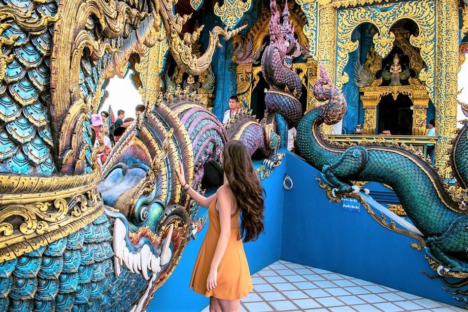 Girl at Blue Temple Chiang Rai, also known as Wat Rong Seua Ten