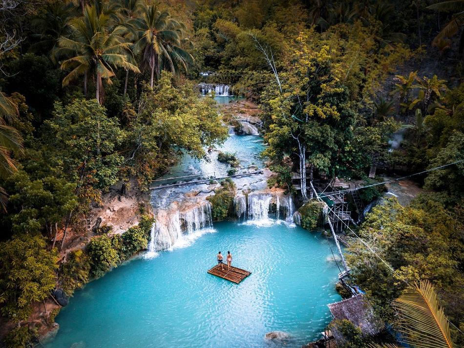 couple on a bamboo raft at Cambugahay Falls, Siquijor