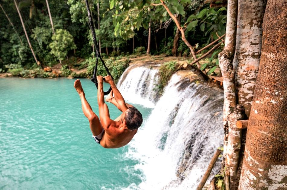 Man on a swing rope at Cambugahay Falls Siquijor
