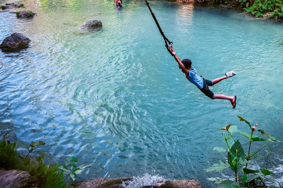 Local swinging at Cambugahay Falls, Siquijor
