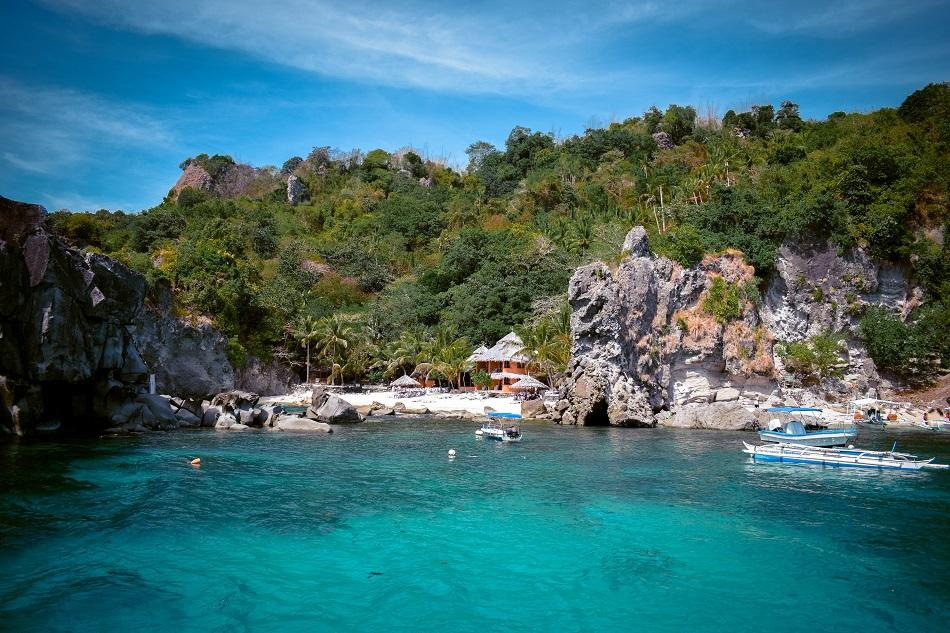 Beach with palm trees and stones at Apo Island, Philippines
