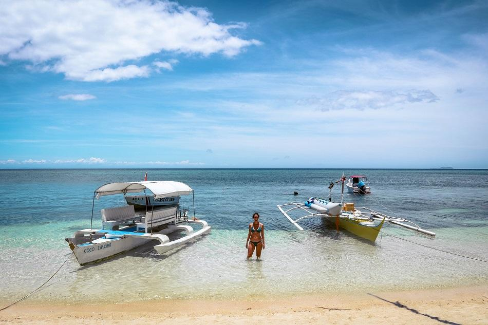 Girl in the water near boats at Paliton Beach Siquijor