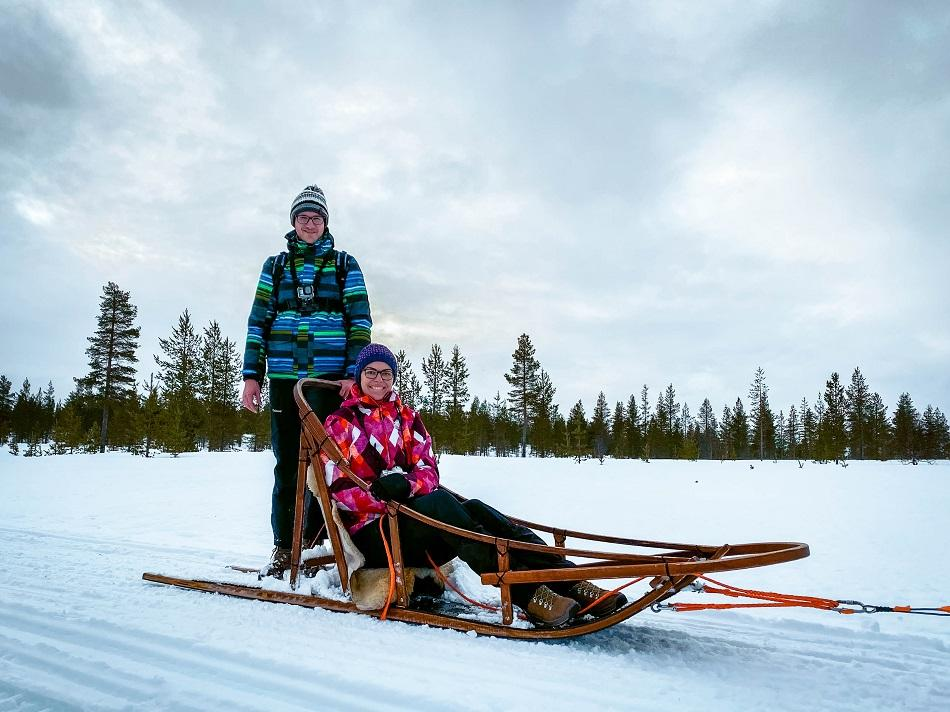 Couple on a sled in snow in Lapland, Finland