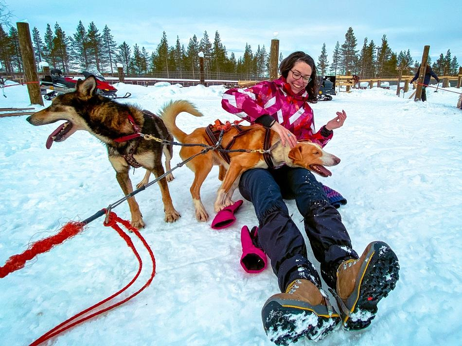 girl playing with sled huskies in Lapland, Finland