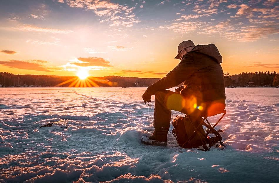 Man ice-fishing at sunset during winter in Lapland, Finland