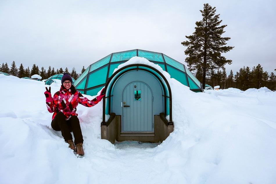 Aurelia Teslaru sitting in front of glass igloo during winter at Kakslauttanen Arctic Resort Lapland