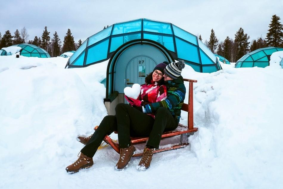 Aurelia Teslaru and Dan Moldovan sitting on a wooden sled in front of a glass igloo during winter at Kakslauttanen Arctic Resort Lapland
