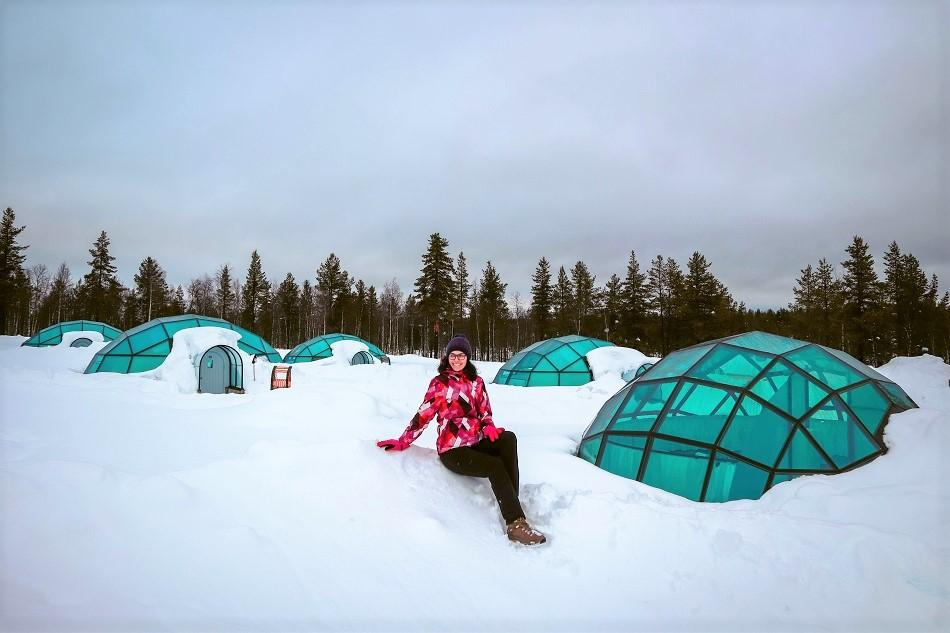 Girl sitting in front of glass igloo village in Lapland in winter at Kakslauttanen Arctic Resort Lapland