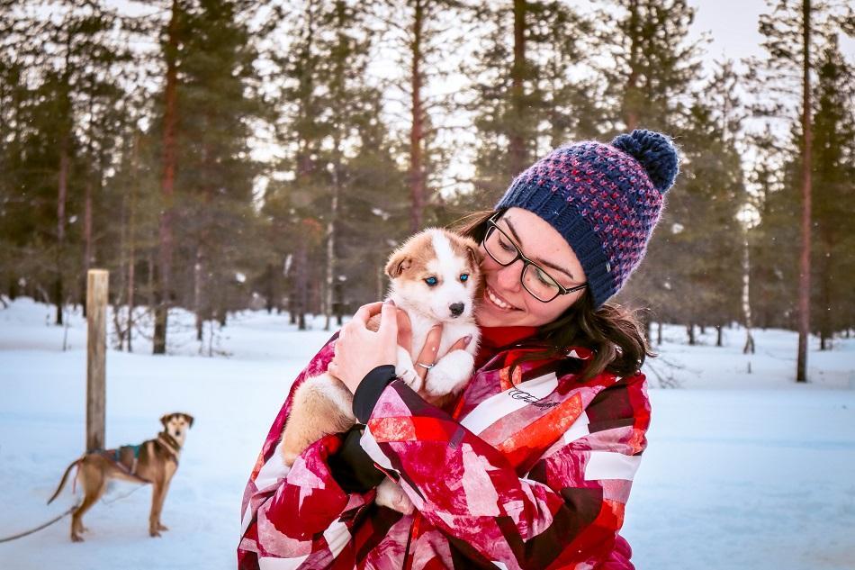 Aurelia Teslaru holding a husky puppy at Kakslauttanen Arctic Resort, Lapland