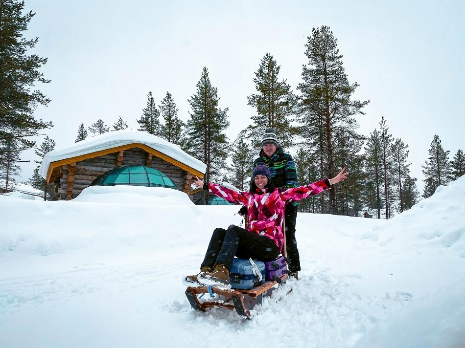 Aurelia Teslaru and Dan Moldovan sitting in front of Kelo Glass Igloo on a sled at Kakslauttanen Arctic Resort Lapland during winter