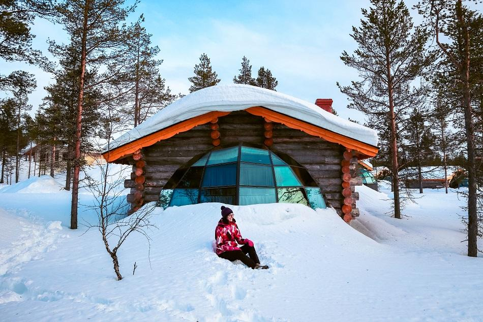 Aurelia Teslaru sitting in front of Kelo Glass Igloo at Kakslauttanen Arctic Resort Lapland during winter