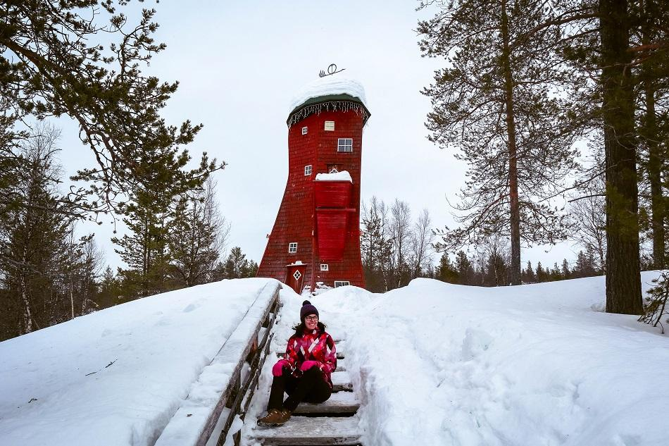 Girl sitting in front of a red elf tower at Kakslauttanen Arctic Resort, Lapland