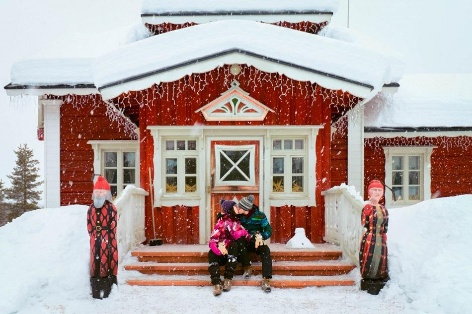 Aurelia Teslaru and Dan Moldovan sitting in front of Santa's home at Kakslauttanen Arctic Resort