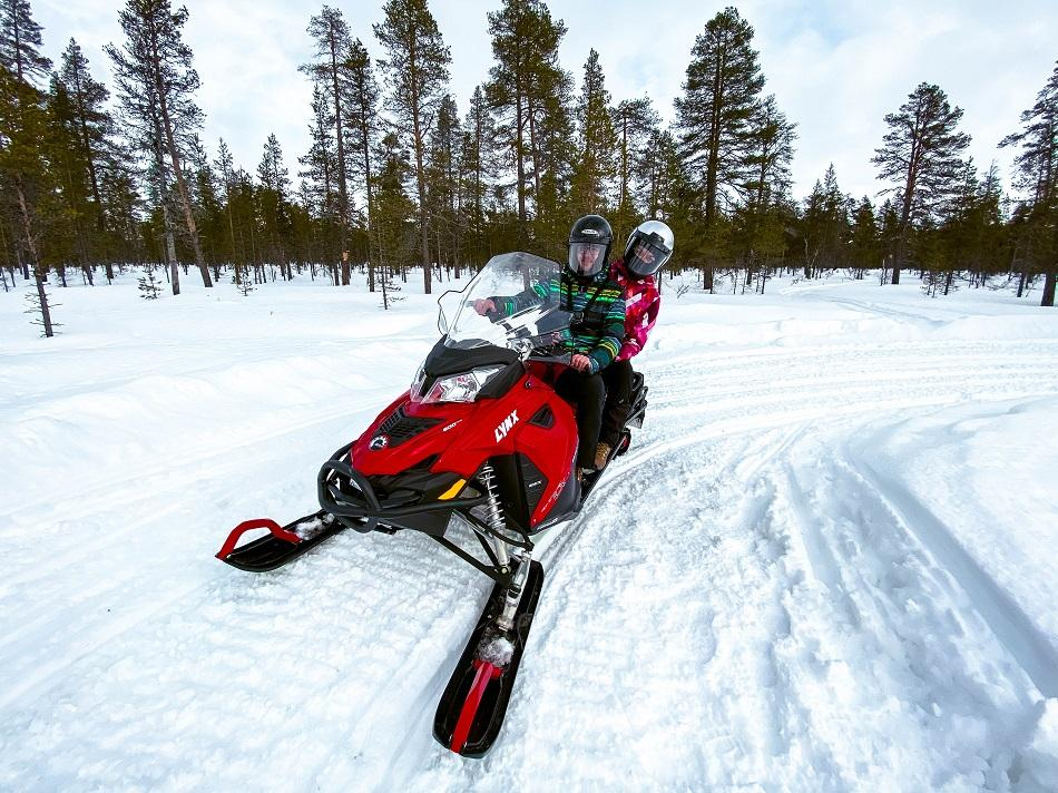 Aurelia Teslaru and Dan Moldovan on a red snowmobile inside the forest in Lapland, Finland