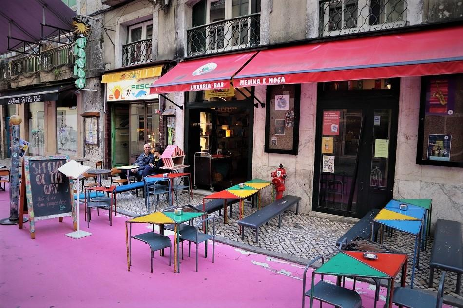 Pink street Lisbon restaurants with tables and chairs outside
