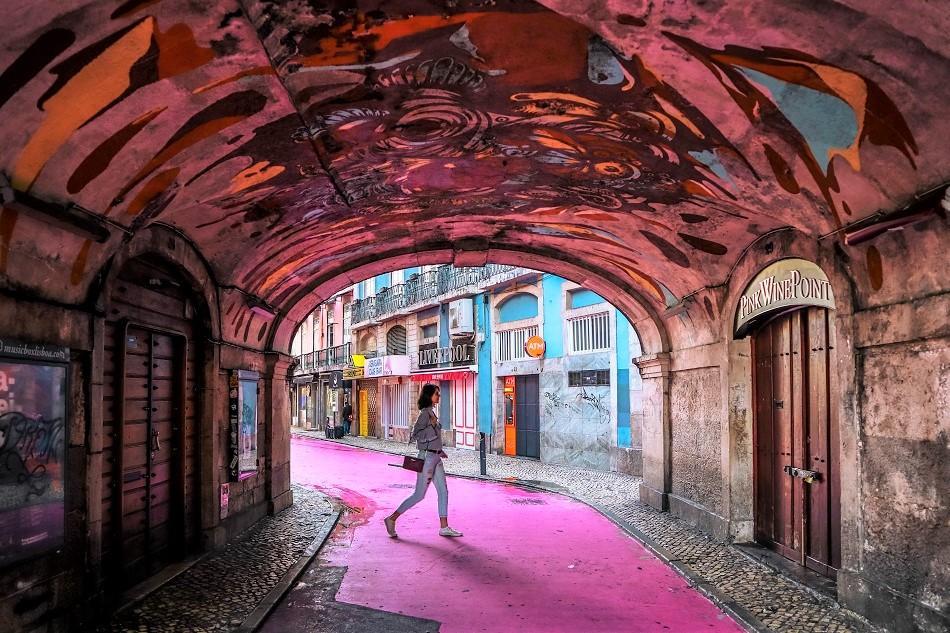 Girl walking on the Pink Street in Lisbon