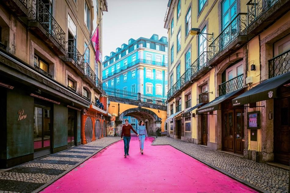 Couple in the middle of Pink Street, Lisbon, also known as Rua Nova do Carvalho
