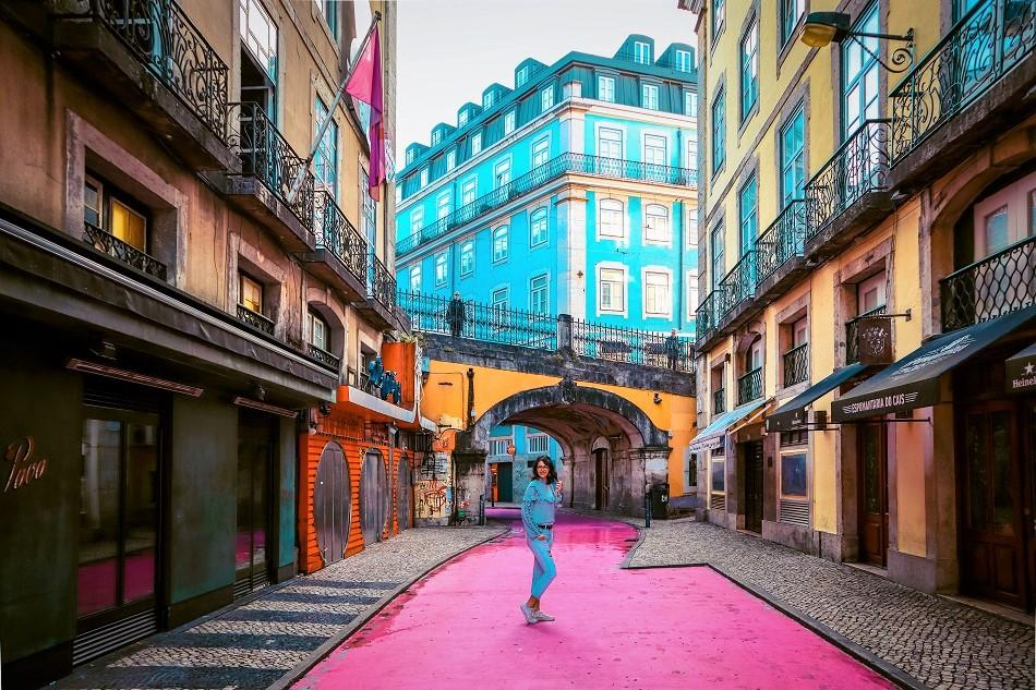 Girl in the middle of Pink Street, Lisbon, also known as Rua Nova do Carvalho