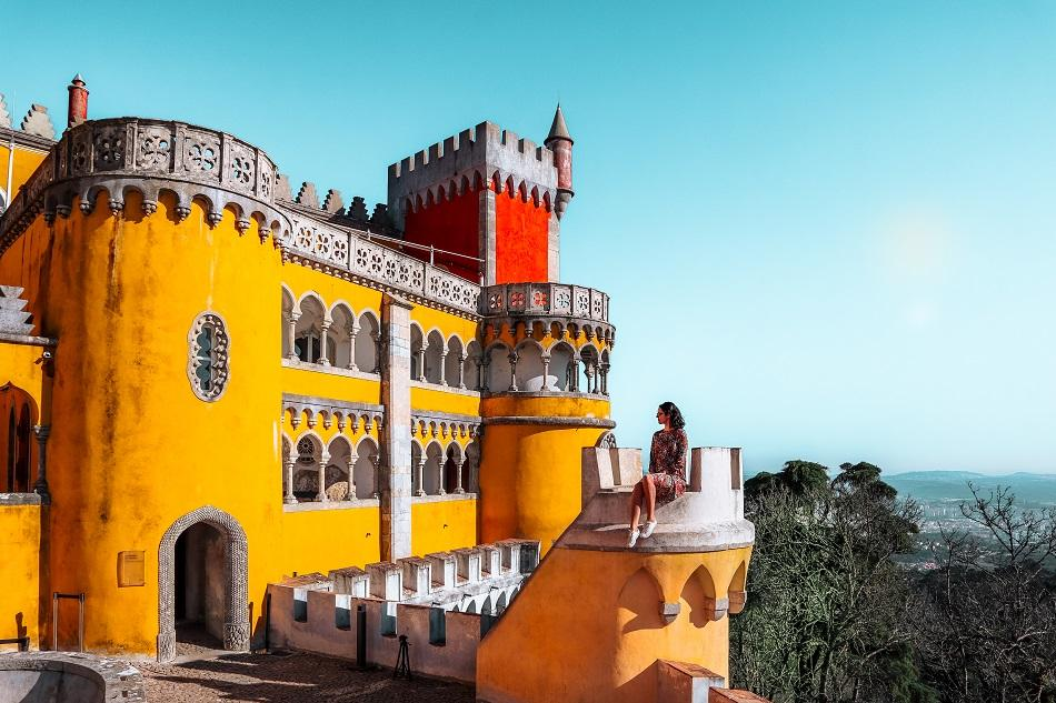 Aurelia Teslaru sitting on a tower at Pena Palace, Sintra