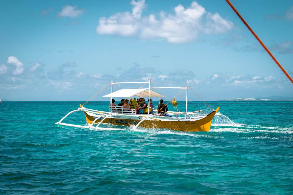 Island Hopping tour in Siargao. Local boat with tourists heading to Guyam Island, Naked Island and Daku Island