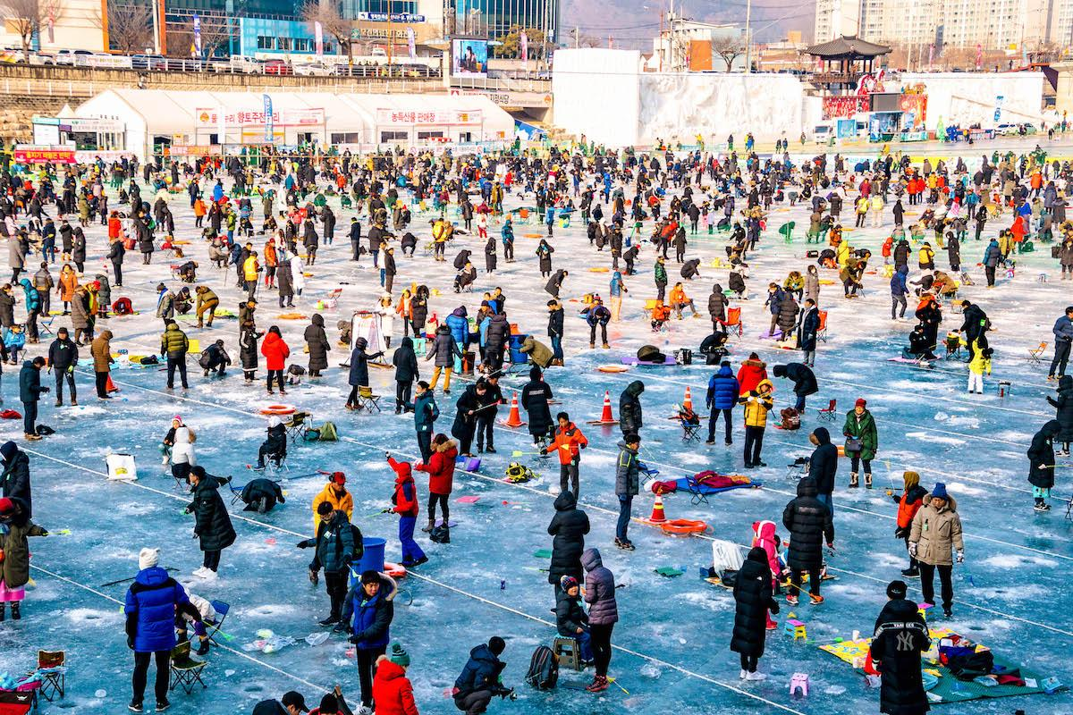Hwacheon Sancheoneo Ice Festival in South Korea. People ice fishing in Korea in winter - things to do in Korea in Winter, winter destinations in Korea, winter activities in South Korea