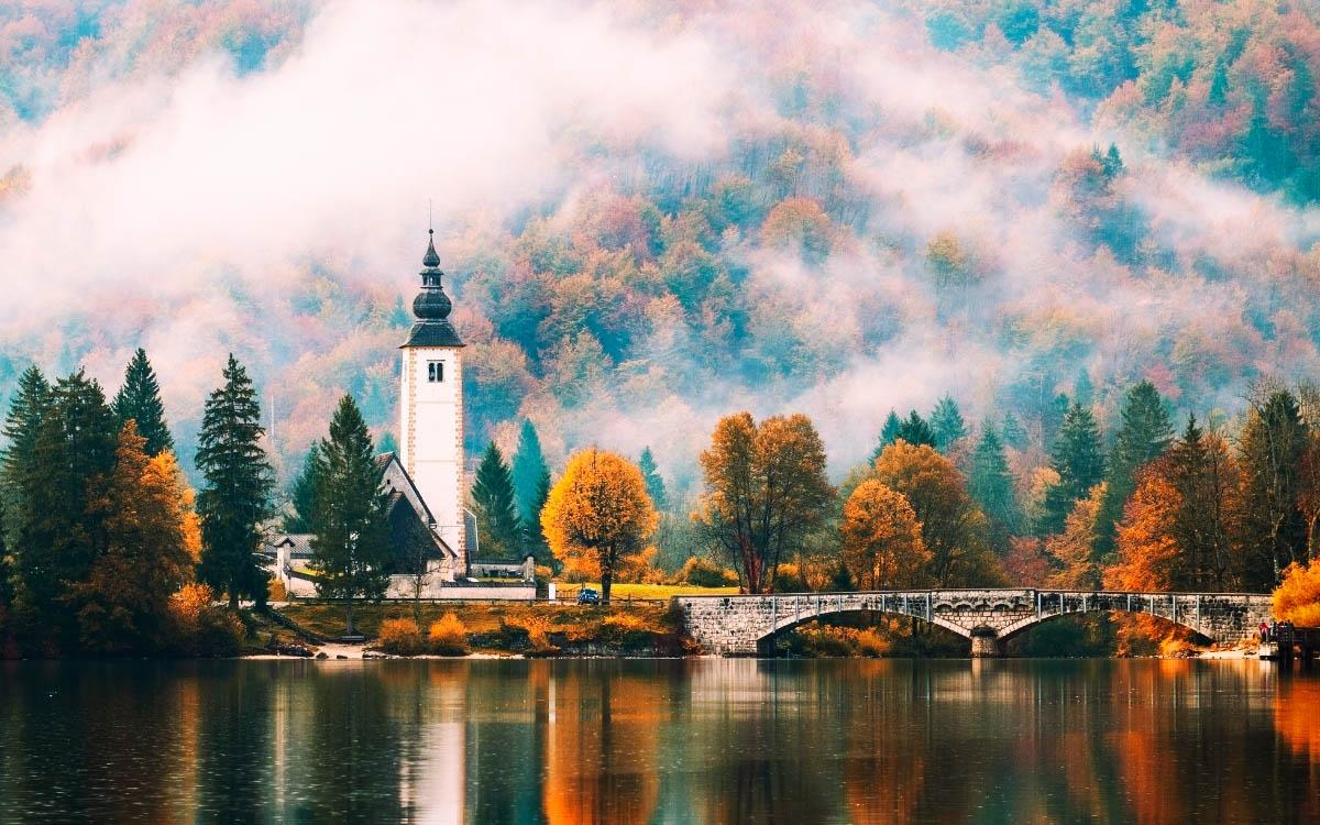 Lake Bohinj Church reflecting into the lake in autumn - hidden gems in Slovenia, off the beaten path, Slovenia off the beaten track, Slovenia secret places, Slovenia unique destinations, less known places in Slovenia