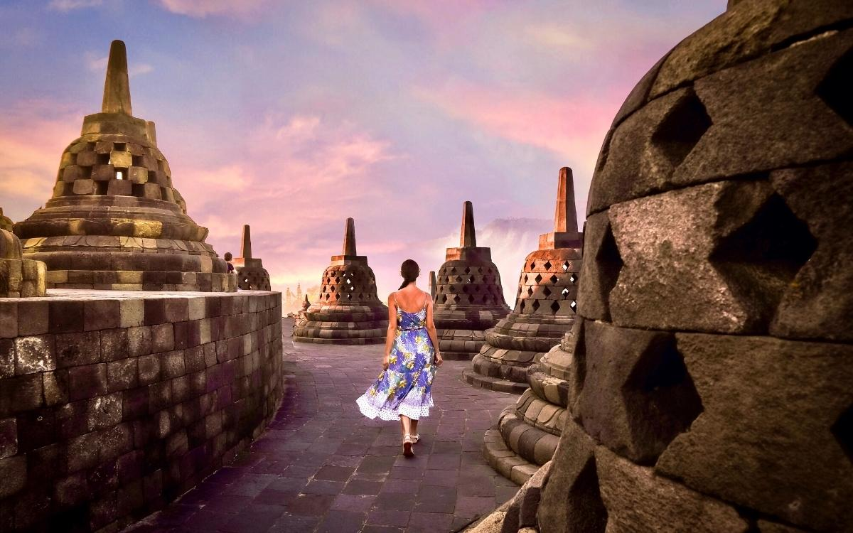 Aurelia Teslaru walking between round stupas at Borobudur Temple Yogyakarta, Java Island. Biggest Buddhist temple in the world
