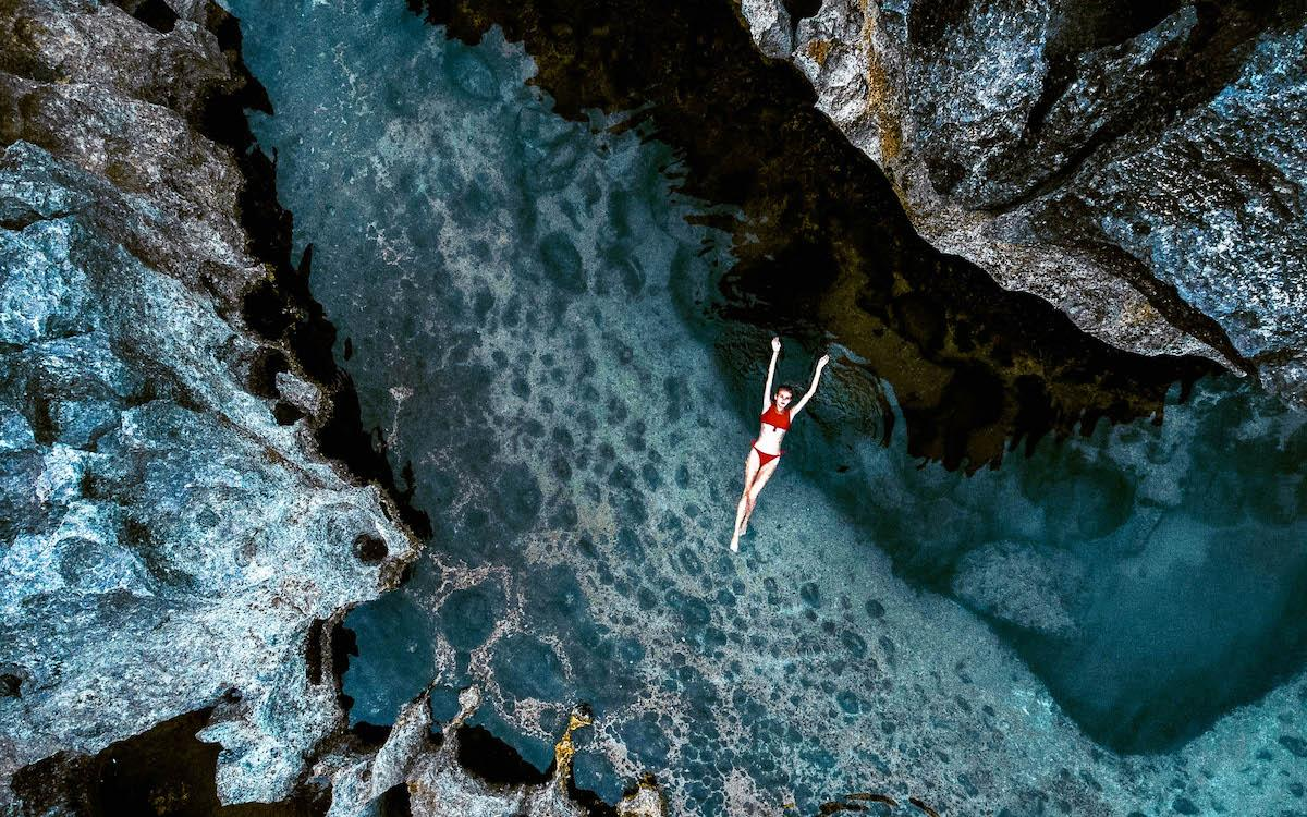 Infinity pool at Angel Billabong Nusa Penida, girl floating in the water