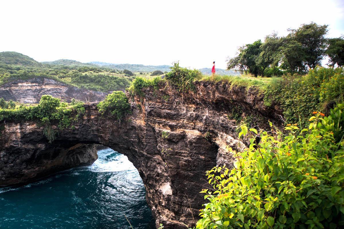 Girl sitting on the edge of the Broken Beach arch in Nusa Penida